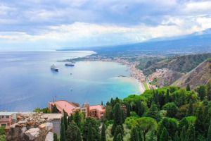 From the old ruins of Taormina, tourists can see the bay of Sicily.