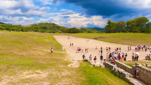 Tourists at the ancient Olympic Stadium in Olympia, Greece.