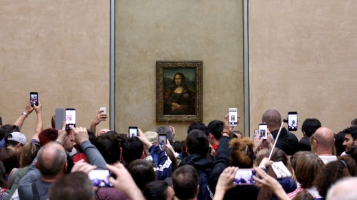 Tourists crowd the Mona Lisa at the Louvre, Paris.