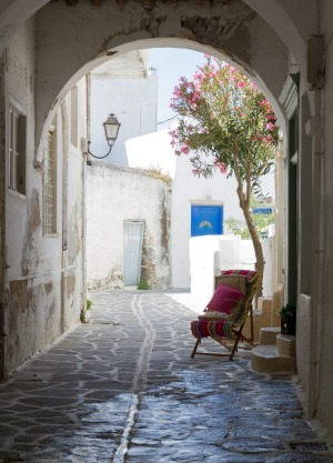Classical narrow street with a painted sidewalk in Parikia.