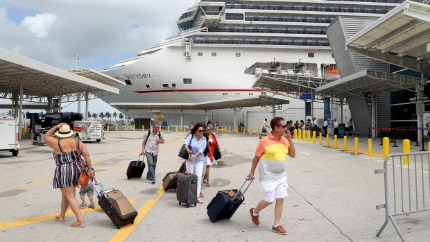 Passengers rush to board Carnival's Victory at the Port of Miami as they prepare to sail for Nassau.