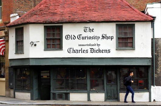 London, England - Sept 11, 2014: A man passes the windows of The Old Curiosity Shop in London, a 16th century building ...