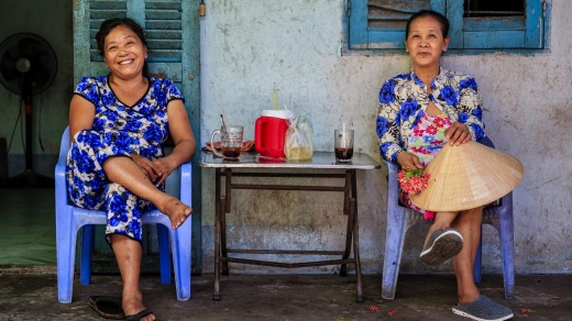 Vietnamese women drinking coffee along the Mekong River Delta, Vietnam.