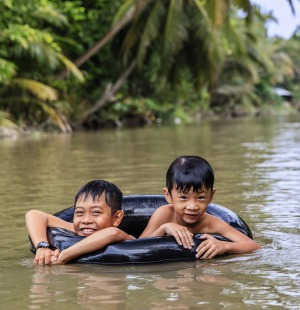 Vietnamese boys playing in the Mekong River Delta, Vietnam.