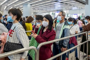 Travellers wear face masks at a train station in Hong Kong.