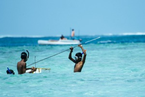 Kids fish in the atolls of the Maldives.