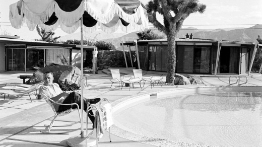 American entertainer Frank Sinatra sits in a deck chair beside the pool at his home and reads a script (for his film ...