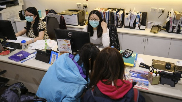Travel agents wearing masks in Melbourne earlier this year. The Australian industry is set to take a $55 billion hit ...