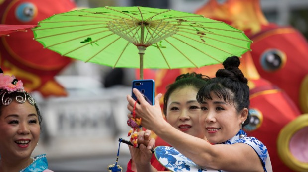 Women in traditional costumes pose for photos ahead of Chinese New Year celebrations in Melbourne.