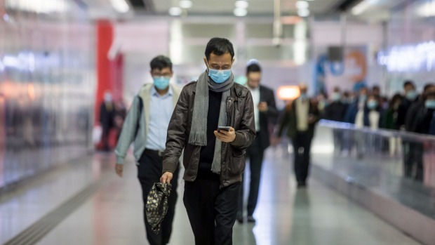 Commuters wearing protective masks walk through Hong Kong Station.