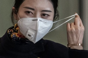A flight attendant adjusts her mask after disembarking from a flight in Beijing.