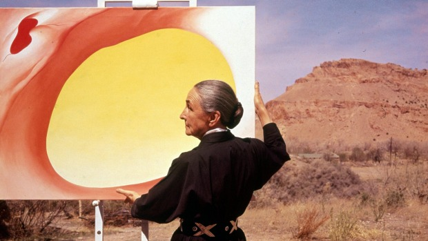 American artist Georgia O'Keeffe (1887 - 1986) stands at an easel outdoors, adjusting a canvas from her 'Pelvis Series- ...