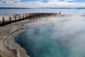 Visitors on a boardwalk that extends into the Black Pool at the West Thumb Geyser Basin, Yellowstone National Park, Wyoming.
