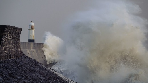 Waves crash against the harbour wall on in Porthcawl, United Kingdom.