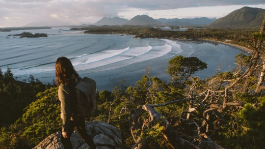 A hiker at Cox Bay overlooking Tofino and the Pacific Rim National Park.