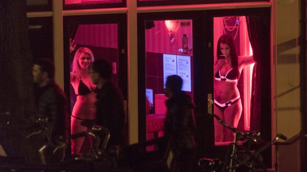 Sex workers are seen behind windows at the red light district in Amsterdam.