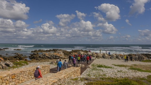 Visitors at Cape Agulhas, the southern-most tip of the African continent and the beginning of the dividing line between ...