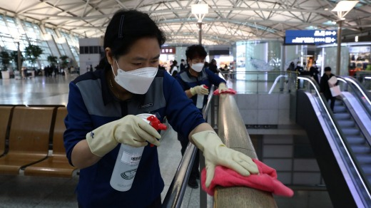 Disinfection workers spray anti-septic solution at Incheon airport.