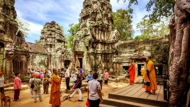 Tourists wander the historic ruins of Angkor Wat in Cambodia.