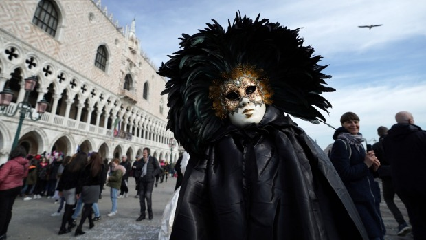 A man wearing a Carnival mask poses in San Marco square during the Venice Carnival last week.
