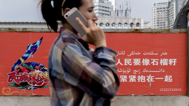 A Uygur woman walks past a propaganda sign in Urumqi, which reads: 'All different peoples should unite together just ...