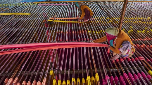 Hanging textiles to dry on bamboo rods in a sari factory.