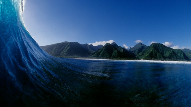 Surfer's view inside a breaking wave with lush green mountain backdrop in Tahiti.