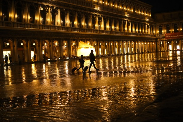 Tourists pull their trolleys as they walk through a nearly empty St. Mark's Square on Monday.