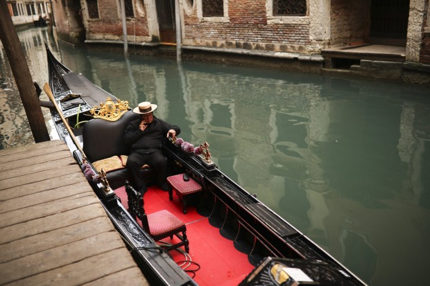 A gondolier talks on his smartphone as he waits for clients in Venice on Saturday.