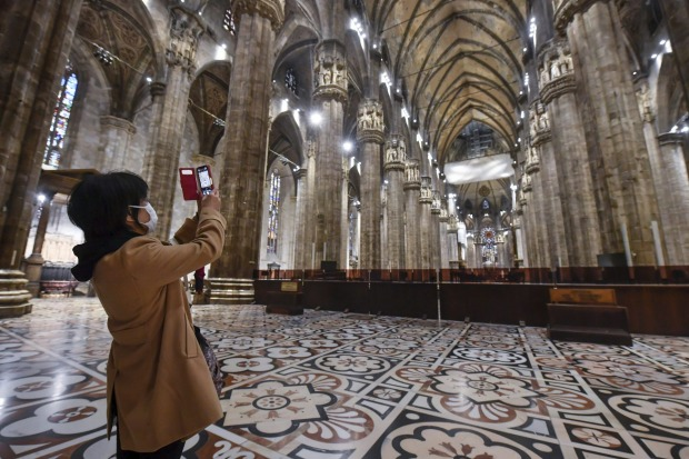 There are few visitors inside Milan's famous Duomo gothic cathedral. It reopened on Monday after being closed due to the ...
