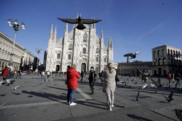 A woman wearing a mask poses for a photo in front of the Duomo gothic cathedral in Milan, Italy.