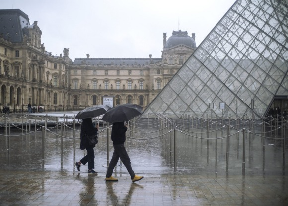 People walk by the Louvre museum, in Paris, France, Sunday, March 1, 2020. The spreading coronavirus epidemic shut down ...