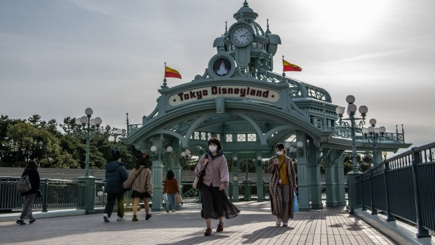 People pass beneath an archway leading to Tokyo Disneyland on the day it announced it will close.