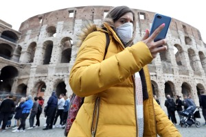A pedestrian wearing a protective face masks walks past the Colosseum in Rome, Italy, on Tuesday, Feb. 25, 2020. Italy ...