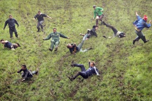 BROCKWORTH, UNITED KINGDOM - MAY 28:  Competitors run and fall down Coopers Hill during the Cheese rolling event on May ...