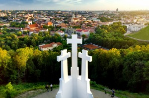Aerial view of the Three Crosses monument overlooking Vilnius Old Town on sunset.