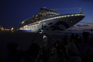 FILE- In this Feb. 10, 2020 file photo, journalists work near the quarantined Diamond Princess cruise ship sitting at ...