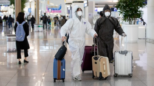 Travelers wearing protective masks and suits walk through Incheon International Airport in South Korea.