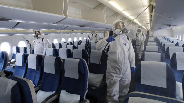 Workers wearing protective gears spray disinfectant inside a plane for New York at Incheon International Airport in ...
