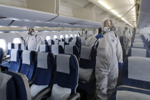Workers wearing protective gears spray disinfectant inside a plane at Incheon International Airport in South Korea.