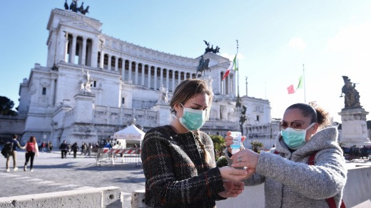 Women wearing face mask disinfect their hands in central Piazza Venezia in Rome.