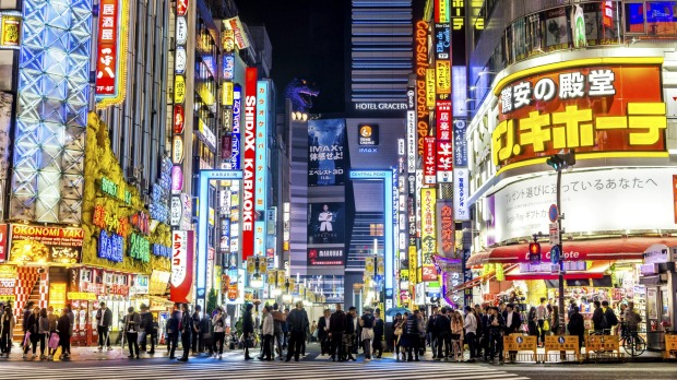 Brightly lit neon signs illuminate the popular nightlife Shinjuku district in Tokyo.