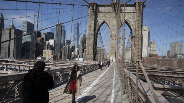 A tourist poses for a photo on the Brooklyn Bridge last year at a time when it is normally packed with tourists and ...