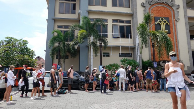 Tourists wear protective mask as they queue up outside the immigration office to extend their visas in Bali.
