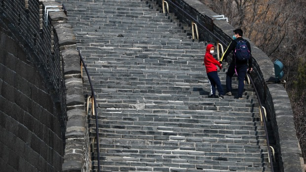 A man and a child wearing protective face masks walk on a stretch of the Badaling Great Wall of China after it reopened ...