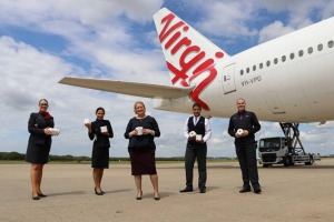 Virgin Australia staff clutch precious cargo, set to be donated to vulnerable people throughout Australia.
