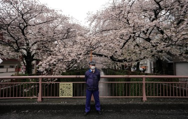 A security person stands on the middle of a bridge on the River Meguro to warn visitors to avoid crowd in Tokyo, Japan, ...