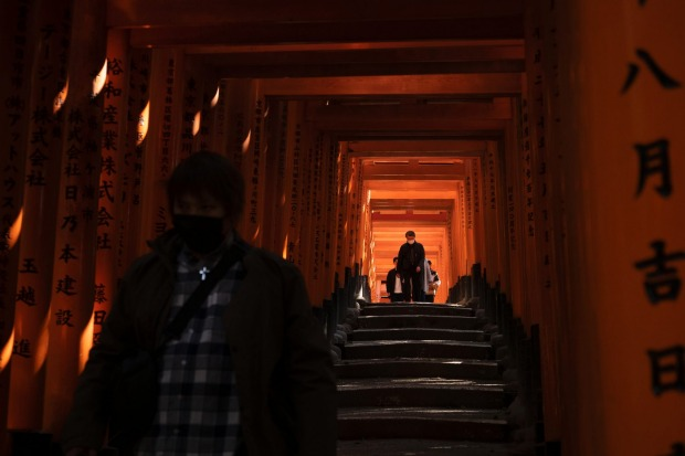 Tourists walk through torii gates at Fushimi Inari Shrine in Kyoto, Japan. Japanese tourism industry has taken a beating ...