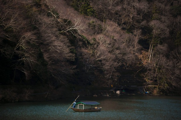 A boatman glides his boat across the river in the Arashiyama district of Kyoto, Japan. Widening travel restrictions and ...