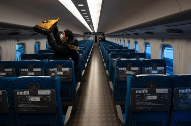 A traveler places his bag in an overhead luggage rack in a bullet train bound for Kyoto and Osaka at Tokyo Station in Tokyo.